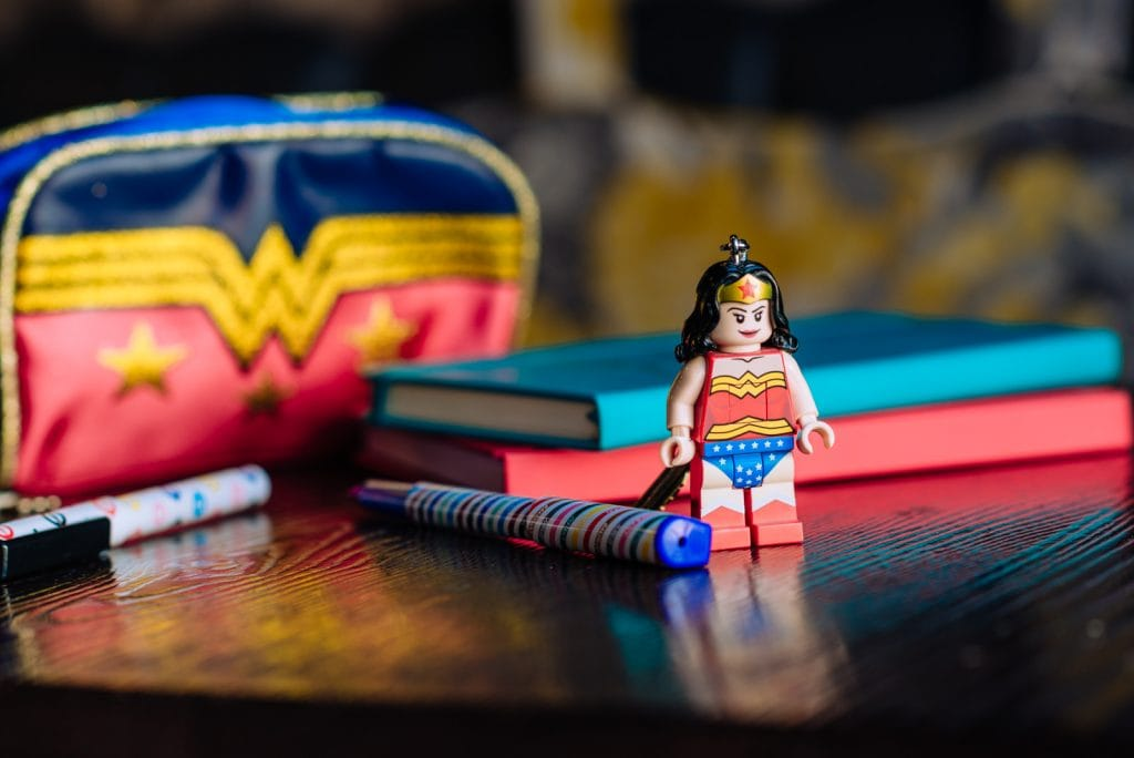 Superwoman figurine next to pile of books and pencil case